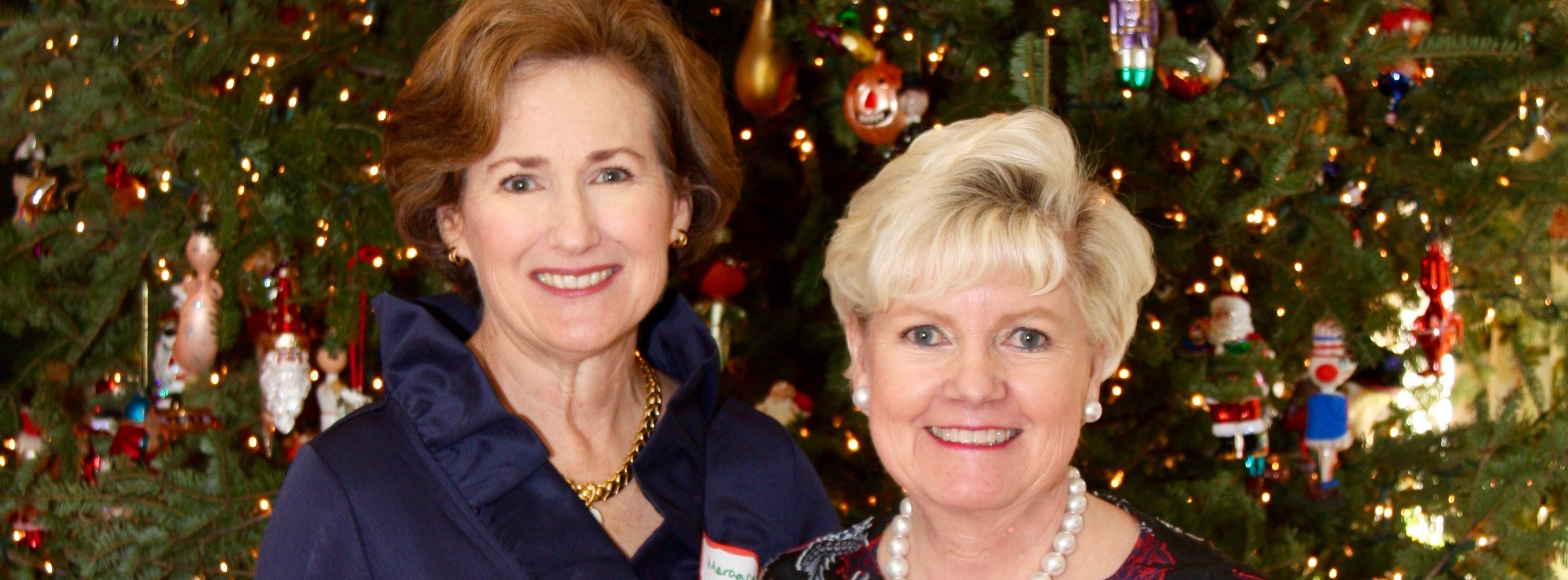 President Margaret Buescher and Christmas Luncheon Hostess Susie Smith smile for the camera in front of Susie's beautiful tree as Thetas, college actives, and Theta moms enjoyed an annual favorite event.